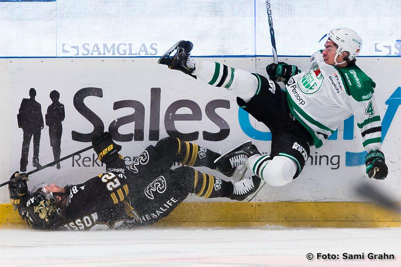 En liggande AIK 22 Daniel Josefsson bjuder Rögle 4 Nils Bergström på en flygtur