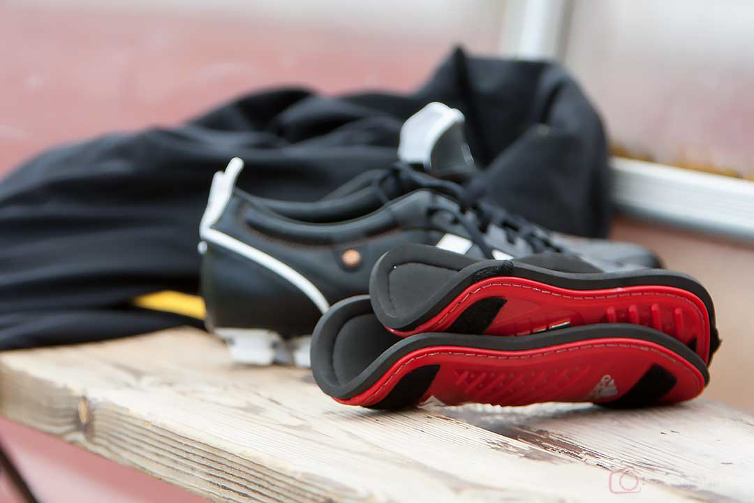 Fotbollsskor och benskydd på bänken