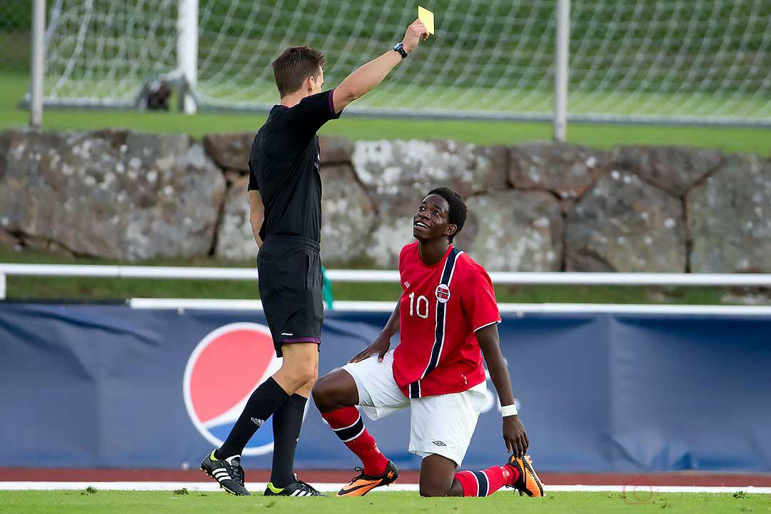 Domare Kenn Hansen delar ut gult kort till planens piggaste spelare, Norge Mushaga Bakenga
