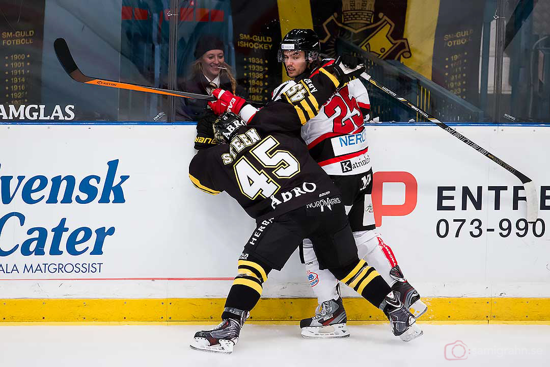 Cecilia ler bakom plexit när AIK Oscar Steen och Örebro Martin Johansson stöter samman