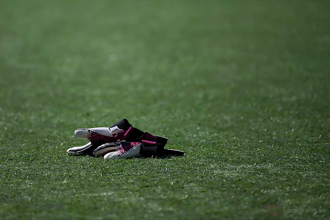 Ett par målvaktshandskar ligger kastade i konstgräset på Grimsta IP