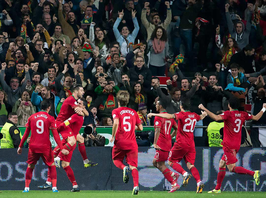 Målskytten Portugal Cristiano Ronaldo gratuleras av laget och hemmasupportrar